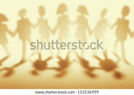 Anonymous paper chain people holding hands - stock photo