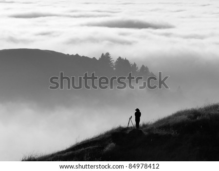 Anonymous silhouette of photographer overlooking a blanket of fog over Pacific Ocean and the Santa Cruz Mountains in California - stock photo