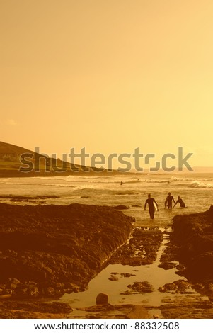 Anonymous surfers  in a small bay in Cornwall - stock photo