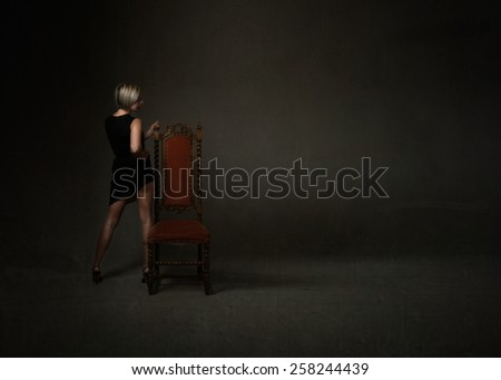 anonymous woman with a chair in a dark room - stock photo