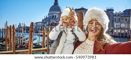Another world vacation. smiling trendy mother and child travellers in Venice, Italy taking selfie while in Venetian mask