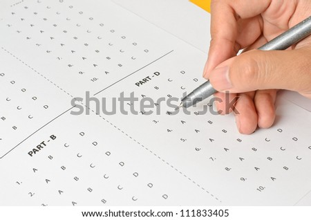 Answer Sheet and hand - stock photo