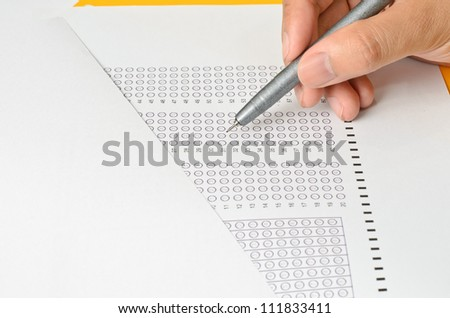 Answer Sheet and Holding Hand with pen - stock photo
