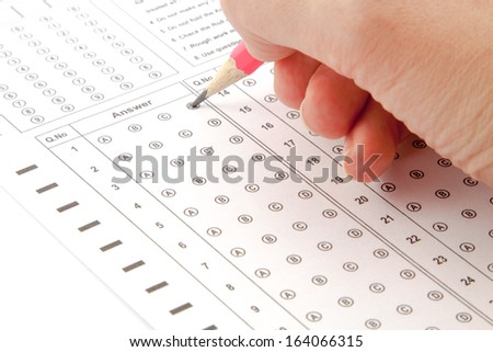 Answer the test with a pink pencil - stock photo