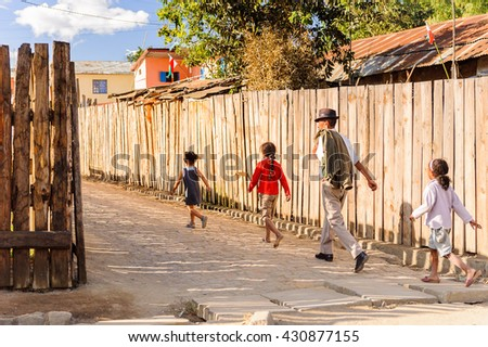 ANTANANARIVO, MADAGASCAR - JUNE 27, 2011: Unidentified Madagascar man and three children walk near the fence. People in Madagascar suffer of poverty due to the slow development of the country - stock photo