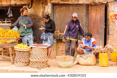 ANTANANARIVO, MADAGASCAR - JUNE 29, 2011: Unidentified Madagascar man and woman work at the fruit market. People in Madagascar suffer of poverty due to the slow development of the country - stock photo