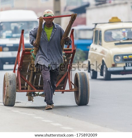ANTANANARIVO, MADAGASCAR - JUNE 28, 2011: Unidentified Madagascar man carries a big carriage. People in Madagascar suffer of poverty due to the slow development of the country - stock photo