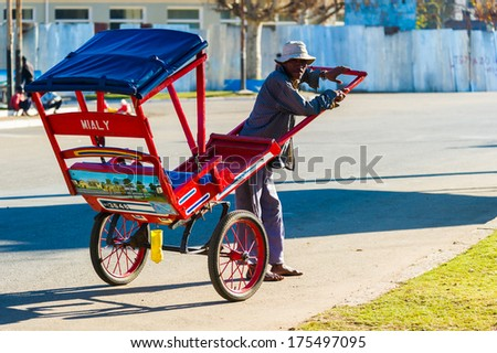 ANTANANARIVO, MADAGASCAR - JUNE 29, 2011: Unidentified Madagascar man carries a carriage. People in Madagascar suffer of poverty due to the slow development of the country - stock photo