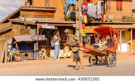 ANTANANARIVO, MADAGASCAR - JUNE 29, 2011: Unidentified Madagascar man carries  a carriage with mother and children. People in Madagascar suffer of poverty due to the slow development of the country - stock photo