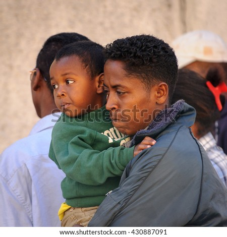 ANTANANARIVO, MADAGASCAR - JUNE 27, 2011: Unidentified Madagascar man carries his little son. People in Madagascar suffer of poverty due to the slow development of the country - stock photo