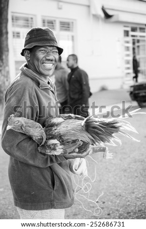 ANTANANARIVO, MADAGASCAR - JUNE 30, 2011: Unidentified Madagascar man holds a hen his hands.  People in Madagascar suffer of poverty due to slow development of the country - stock photo