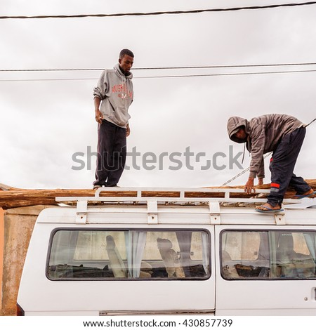 ANTANANARIVO, MADAGASCAR - JUNE 29, 2011: Unidentified Madagascar man on the top of a minivan. People in Madagascar suffer of poverty due to the slow development of the country - stock photo