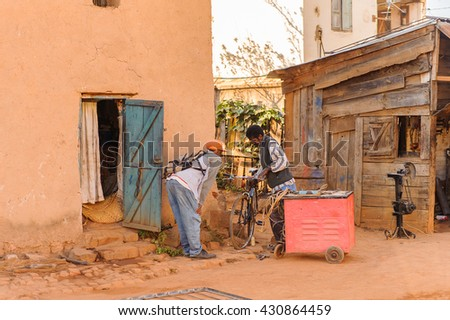 ANTANANARIVO, MADAGASCAR - JUNE 29, 2011: Unidentified Madagascar man tries to sell a bicycle to a friend. People in Madagascar suffer of poverty due to the slow development of the country - stock photo