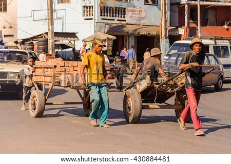 ANTANANARIVO, MADAGASCAR - JUNE 27, 2011: Unidentified Madagascar men carry the huge carriage, People in Madagascar suffer of poverty due to the slow development of the country - stock photo