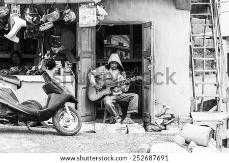 ANTANANARIVO, MADAGASCAR - JUNE 29, 2011: Unidentified Madagascar shop seller plays guitar. People in Madagascar suffer of poverty due to the slow development of the country