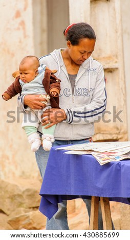 ANTANANARIVO, MADAGASCAR - JUNE 29, 2011: Unidentified Madagascar woman carries her baby and reads a newspaper. People in Madagascar suffer of poverty due to the slow development of the country