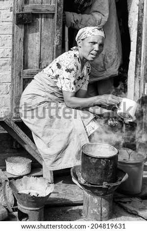 ANTANANARIVO, MADAGASCAR - JUNE 30, 2011: Unidentified Madagascar woman makes rea and hot water. People in Madagascar suffer of poverty due to slow development of the country