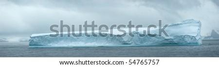 Antarctic ice island with penguins  in atlantic ocean - stock photo