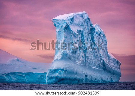 Antarctic iceberg in the snow floating in open ocean. Pink sunset sky in the background. Beauty world