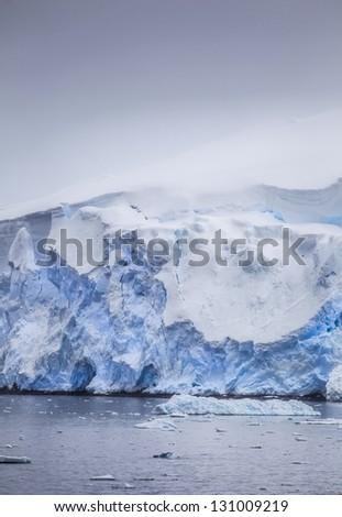 Antarctic icebergs with snowdrifts - stock photo