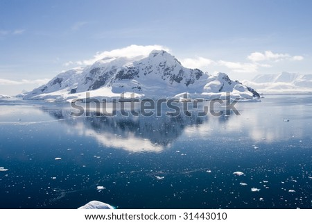 antarctic mountain with glacier is reflected in paradise harbour - stock photo
