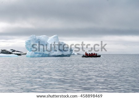 ANTARCTICA - CIRCA JANUARY 2015: Inflatable boat carrying Antarctic cruise passengers in red jackets past an iceberg