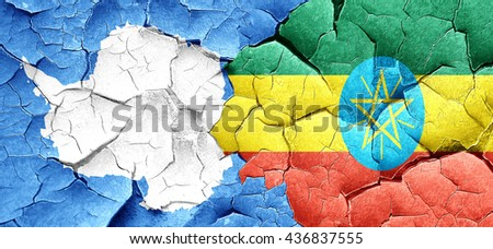 antarctica flag with Ethiopia flag on a grunge cracked wall - stock photo
