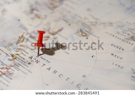 Antarctica South Pole marked on map with red pushpin. Pin casts harsh shadow to the right and is slightly angled to the right. Queen Maud Land can be seen on map.