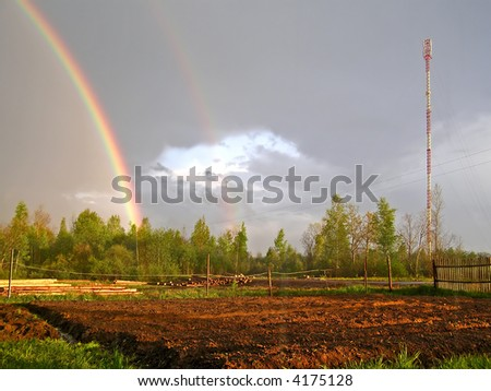 antenna and rainbow in rural terrain