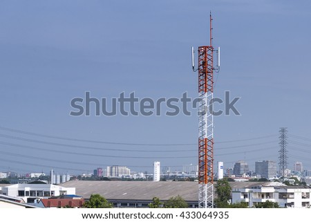 antenna tower building with the blue sky.The antenna pole in the city with the sky.The radio antenna tower in the city.The red-white antenna building with the blue sky and city background - stock photo