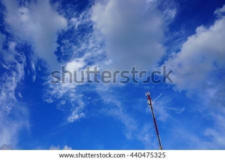 Antenna tower building with the blue sky. The antenna pole with the sky. The red-white antenna building with the blue sky background - stock photo