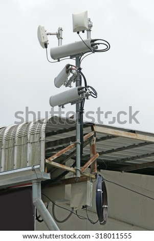 Antennas of mobile cellular systems with wifi hot spot repeater and blue sky - stock photo