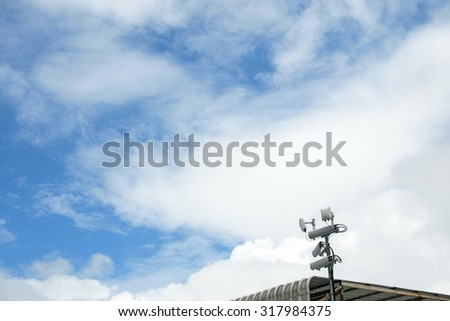 Antennas of mobile cellular systems with wifi hot spot repeater and cloudy blue sky - stock photo