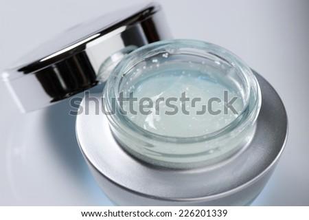 Anti-aging serum in opened glass jar. - stock photo