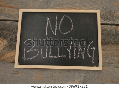Anti-bully message or no bullying written in chalk on a chalkboard on a rustic background - stock photo