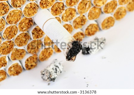 anti smoking concept, focus on the burnt cigarette, easily converts to sepia or black and white - stock photo