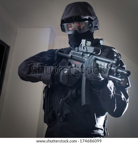 Anti terrorist unit policeman during the night strike/operation/mission in criminal's house aiming at the target (very harsh lighting is used on this shot to underline the atmosphere of night mission) - stock photo