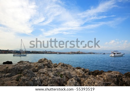 Antibes at the Côte d'Azu, seen from Cap d'Antibes, small yacht and sailboat anchored in the bay, rocks in foreground - stock photo