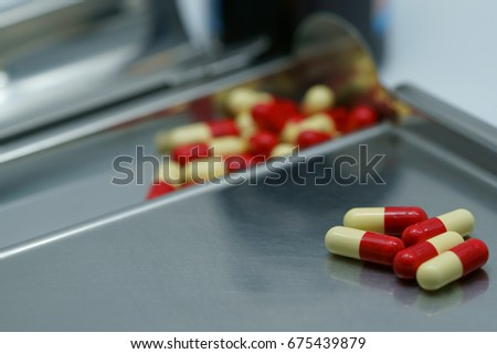 Antibiotic capsule pills on  stainless steel drug tray. Drug resistance concept design.