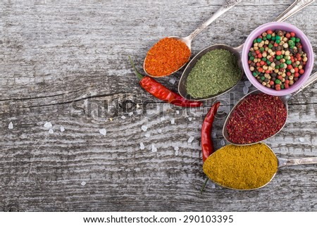 Antic metal spoons and small bowl with different kinds of spices on old wooden board. Selective focus. - stock photo