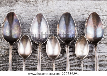 Antic metal spoons on old wooden board. Selective focus. - stock photo