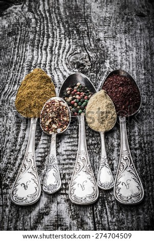 Antic metal spoons with different kinds of spices on old wooden board. Selective focus. Toned.