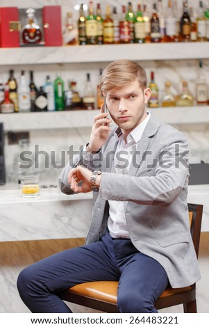 Anticipating a meeting. Young man in shirt and jacket talking over the phone and looking at his watch while sitting at the counter of the bar - stock photo