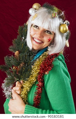 Anticipation of Christmas - blessed looking woman holding a fir branch. - stock photo