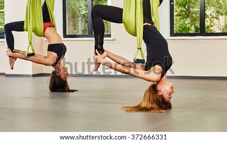 Antigravity yoga exercise. twwo girls - stock photo