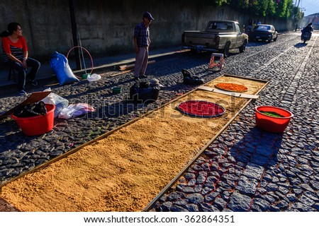 Antigua, Guatemala -  April 3, 2015: Locals make carpet (alfombra) of dyed sawdust for Good Friday procession in Spanish colonial town with most famous Holy Week celebrations in Latin America.