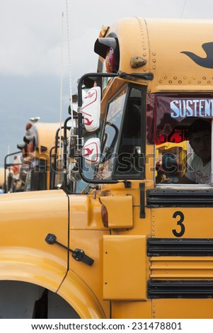ANTIGUA, GUATEMALA - CIRCA OCTOBER 2012: Brightly decorated local buses (chicken buses) at city bus station - stock photo