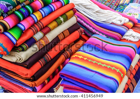 Antigua, Guatemala - May 6, 2012: Typical brightly colored handwoven Guatemalan textiles (bedspreads & hammocks) for sale by local indigenous people at an open air street market in Antigua, Guatemala