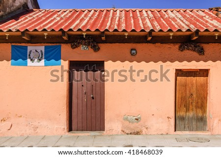 Antigua, Guatemala - October 5, 2014: Old, painted house adorned with Guatemalan flag in colonial city & UNESCO World Heritage Site of Antigua.