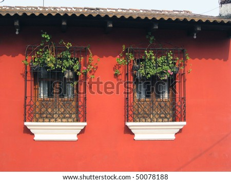 Antigua Windows-Against a bright orange wall blend Indian and Spanish colonial flair - stock photo